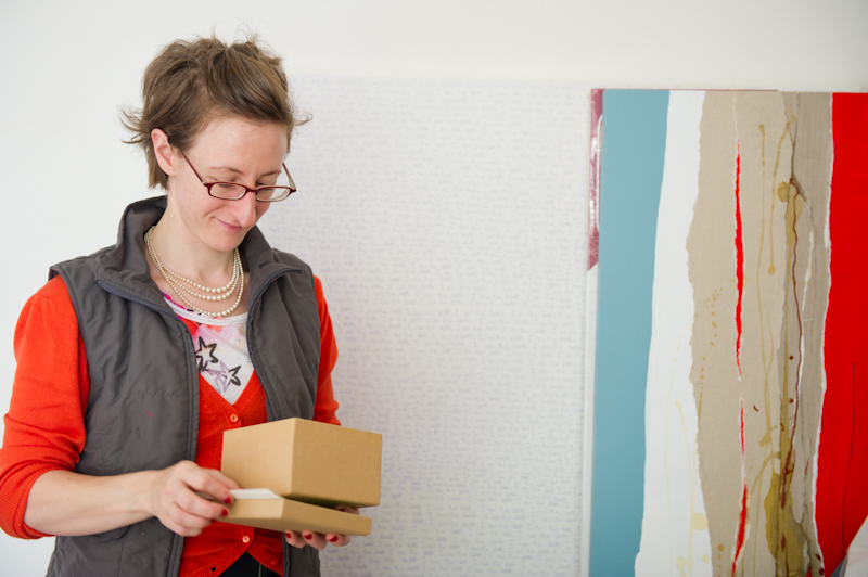 Emily with a gift box next to her artworks in the studio