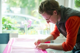 Emily tending to the wrapping of an artwork for a valued customer