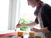 Emily Pitts painting a canvas in the window of the studio